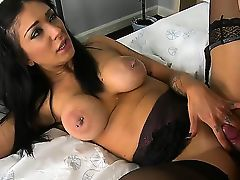 Long haired brunette mistress with great big boobs and pierced nipples dressed in