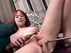 Beautiful redhead is laying down on the floor and is fucking with her machine dildo